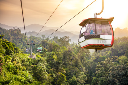 Aerial tramway moving up in tropical jungle mountains