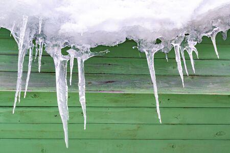 Foto de Icicles are icy against backdrop of old wooden wall. - Imagen libre de derechos