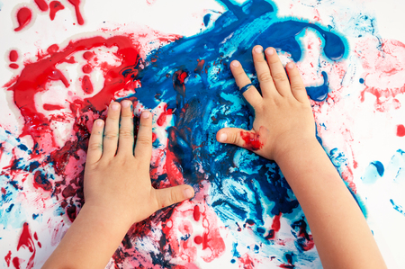 Photo pour Painted hands smudging colors on messy paper . - image libre de droit