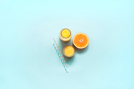 Freshly squeezed orange juice on a turquoise background. Copy space