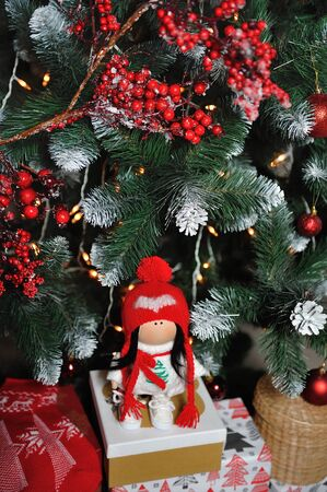 Photo pour A cute children's soft doll in a red hat stands next to a Christmas tree. New Year's gift children's soft doll - image libre de droit