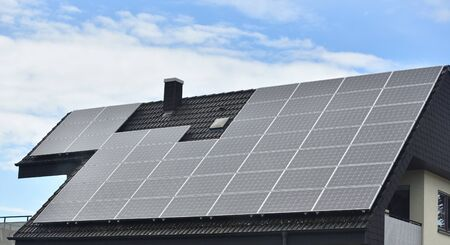 Photo for Solar panels installed on the roof of a house with tiles in Europe against the background of a blue sky. - Royalty Free Image