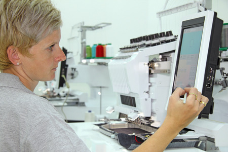 Photo pour Woman working on computerized machine embroidery in a factory - image libre de droit