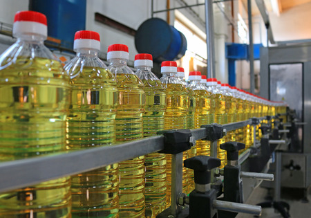 Photo pour Sunflower oil in the bottle moving on production line - image libre de droit