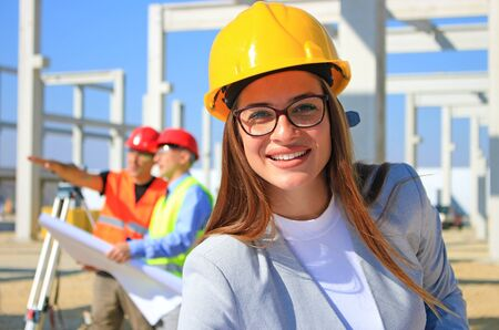 Photo pour Happy beautiful female architect on construction site. She is smiling and satisfied with her job, behind her construction engineers planning and talking about the project, teamwork - image libre de droit