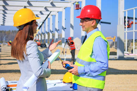 Photo for Female architect and construction engineer in hardhats talking about the project on construction site, behind them construction worker with measuring device, crane and construction workers, teamwork - Royalty Free Image