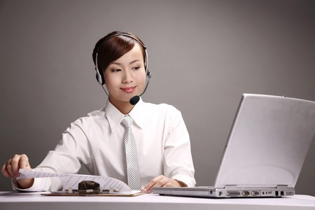 Businesswoman wearing headset checking documents on clipboard