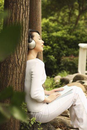 Photo pour Woman leaning against tree, listening to music on the headphones - image libre de droit