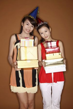 Two young women holding stacked up gift boxes