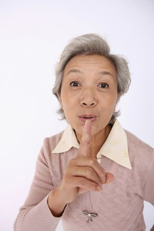 Senior woman with finger over her mouth