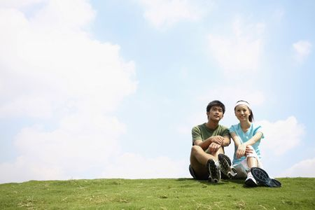 Photo for Man and woman sitting on the field - Royalty Free Image