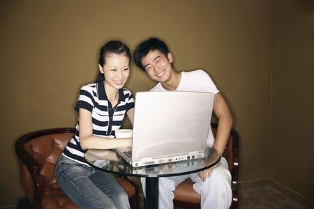 Man and woman using laptop, laughing