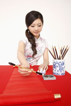 Woman in cheongsam writing New Year's greeting