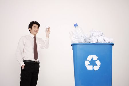 Man trying to throw crumpled paper into recycle bin