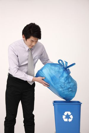 Man throwing a plastic bag of trash into the recycling bin