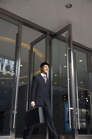 Businessman with briefcase walking out of a building