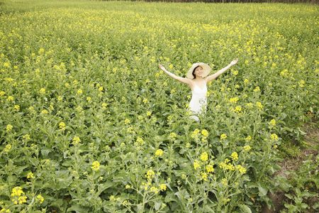Woman standing at the rape field with her arms outstretched