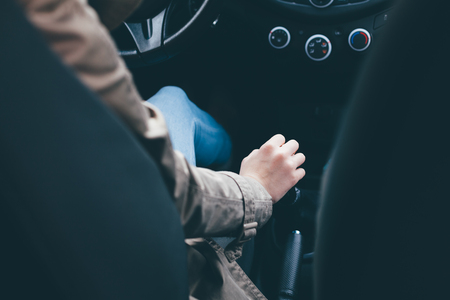 Hand on transmission. Woman driving car.