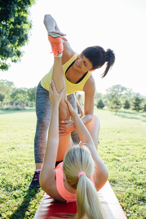 Beautiful fitness female trainer working out with beginners