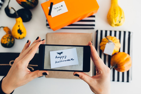 Woman take a picture of Happy Halloween Greeting Card on Wrapped Presents