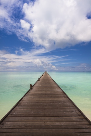 wooden jetty leading over the turquoise sea to the horizon