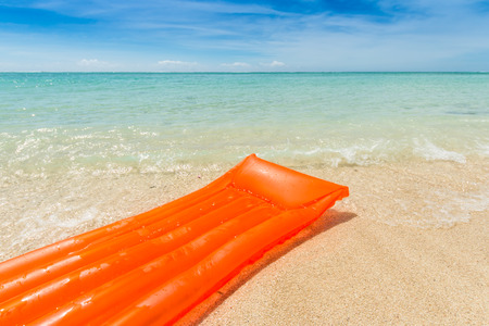travel background with a orange air mattress; sand of the beach and turquoise sea a under a blue sky, Le Morne, Mauritius, Africa