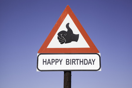 red and white warning triangle traffic sign with a human hand showing thumb up and the words happy birthday, concept for congratulation and compliments
