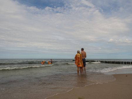 Mielno, Poland - July 31, 2016: Parents / pair standing on  a shore and  watching their  children bathing