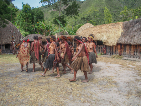 Photo for Wamena, Indonesia - January 23, 2015: Dani tribe women dancing in the front of their house - Royalty Free Image