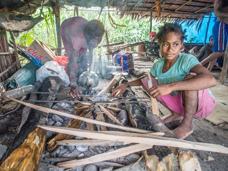 Jungle, Indonesia - January 13, 2015: Two girls from the Korowai tribe preparing the food on the fire place inside the wooden house. West Papua, Indonesia