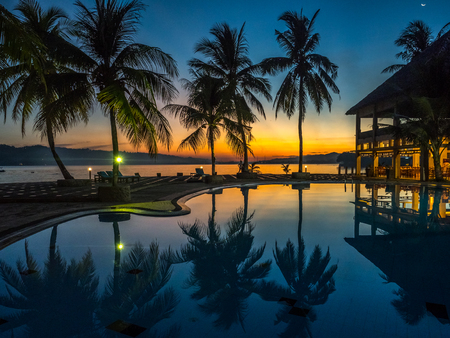 View with silhouettes of  palm trees around luxury swimming pool during a tropical sunset. Ambon Island. Indonesia