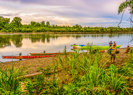 Jungle, Indonesia - January 13, 2015: Colourful boats  on the banks of the river during the sunset.