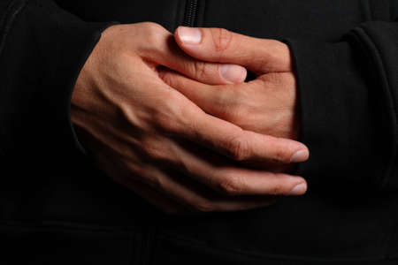 Folded hands of a priest