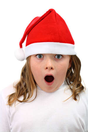 Surprised girl in Santa's red hat isolated on whiteの写真素材