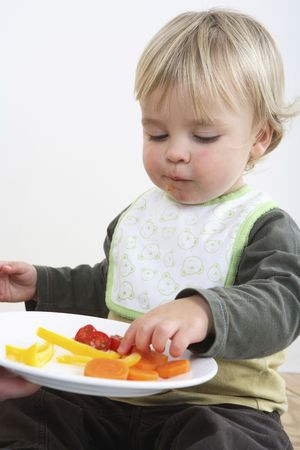 Preschooler with  bib eating vegetables