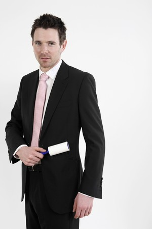 Businessman using lint roller on his coat