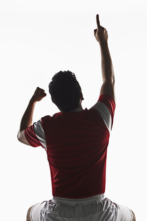 A soccer player point his finger to the air