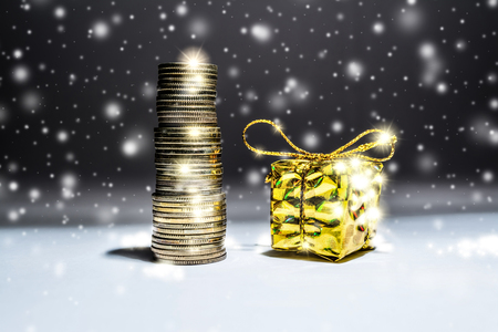 Foto de New Year's still-life with a stack of gold coins and a box with a gift on a dark background with falling snow - Imagen libre de derechos