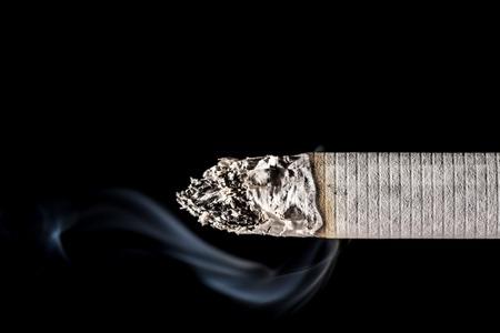 Photo for Burning smoldering cigarette close-up with beautiful smoke isolated on black background - Royalty Free Image
