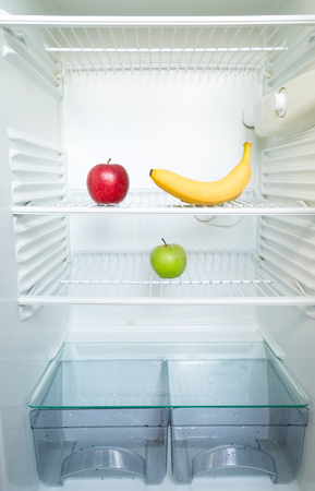 Photo pour Bright fresh red and green apples and banana on shelf of open empty refrigerator. Weight loss diet concept. - image libre de droit