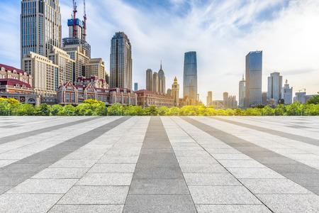 empty pavement and city skyline under blue sky