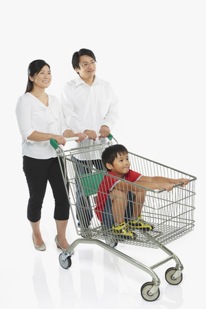 Parents pushing a shopping cart with son in towの写真素材