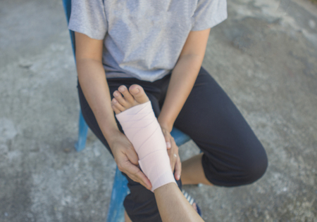 Volunteers are provided to patient ankle wrap Elastic Bandage, with patient ankle injury.