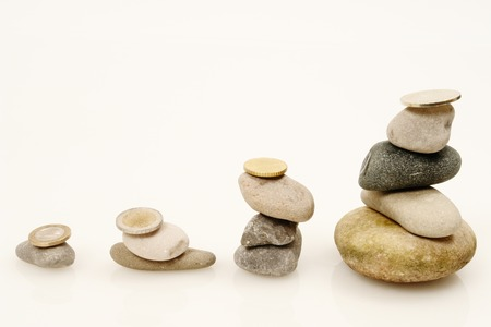 Coins and Pebbles on white as a symbol for financial balance