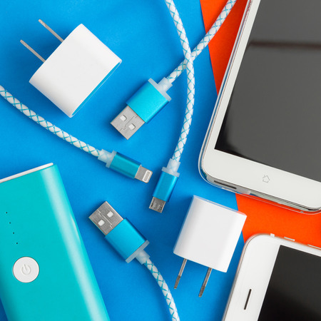 Photo pour USB charging cables for smartphone and tablet in top view on blue and orange background - image libre de droit