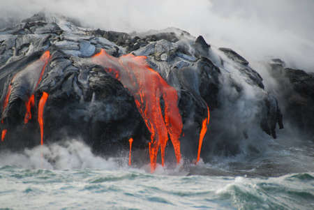 Red hot lava from Kilauea Volcano on the Big Island of Hawaii flows through lava tubes and pours like rivers into the ocean, bringing up clouds of steam and toxic gas, creating acres of lava rock and adding new land to the island.