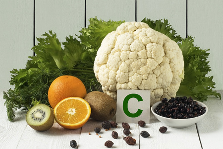Foods rich in vitamin C: currants, dried rosehips, cauliflower, lettuce, dill, orange, kiwi on a light background