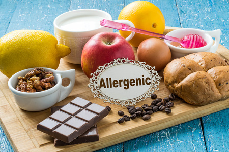 Photo pour Concept of food allergies. Set of products that cause allergies: citrus, red fruits and berries, eggs, milk, white bread, nuts, chocolate, coffee, honey - image libre de droit