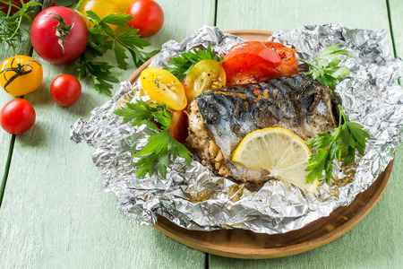 Photo pour Mackerel baked with tomatoes in foil. Mackerel in foil lies on wooden plate on green wooden table. Also lie fresh tomatoes and herbs. Healthy and dietary food - image libre de droit