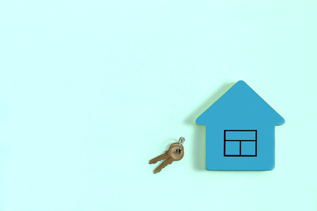 Blue block of paper for notes in shape of house with picture window and keys on pastel blue background. Minimal style. Concept of sale or purchase of real estate. Copy space